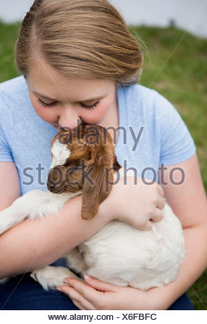 A girl cuddling a baby goat. - Stock Photo