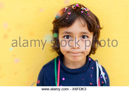 Little boy pulling funny face in front of yellow wall while confetti falling down on him - Stock Photo