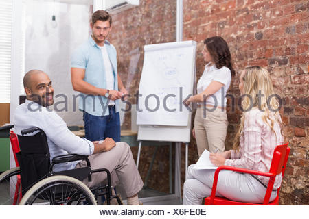 Man in wheelchair smiling at camera during presentation - Stock Photo