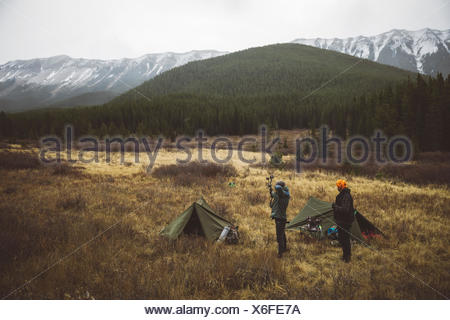 Male hunter friends outside tents at campsite in remote field below mountains - Stock Photo