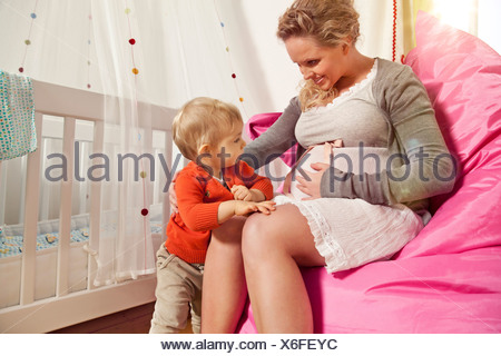 Germany, Bonn, Pregnant mother explaining her belly to son, smiling - Stock Photo