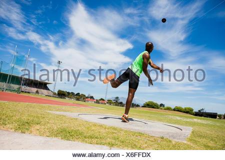 Male athlete throwing shot put ball - Stock Photo