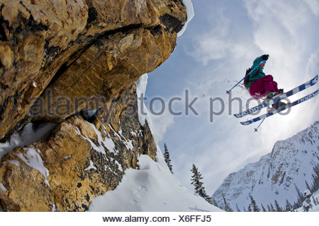 A female skier flys off a cliff at Kicking Horse Resort, Golden, BC - Stock Photo