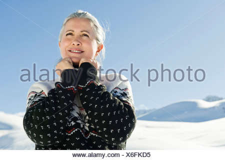 Italy, South Tyrol, Seiseralm, Senior woman, hands on chin, smiling, portrait - Stock Photo