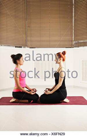 Women relaxing in yoga class - Stock Photo