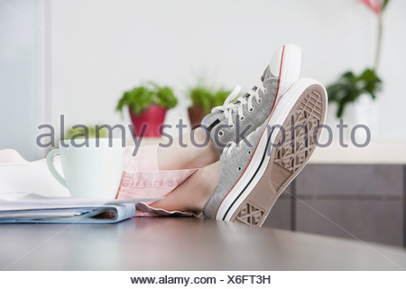 detail of young woman relaxing at home with feet on the table - Stock Photo