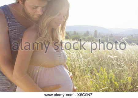 Young man touching pregnant girlfriends stomach in field - Stock Photo