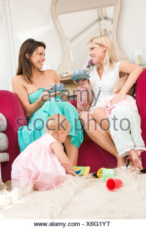 Two mothers in living room with babies and coffee smiling - Stock Photo