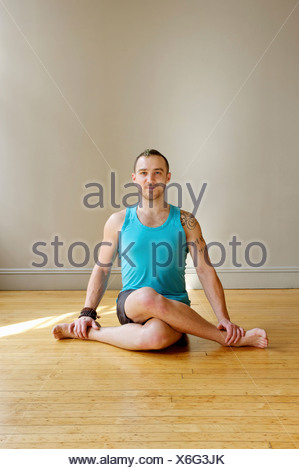 Man in Cowface yoga pose - Stock Photo