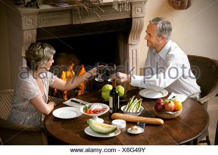 Mature couple sitting at laid table toasting with red wine in front of open fire - Stock Photo