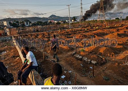 Gravediggers pause after a long day of Ebola outbreak burials in a Freetown cemetery. - Stock Photo