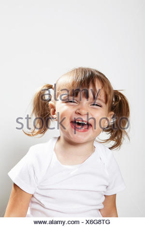 Portrait of young girl with pigtails, laughing - Stock Photo