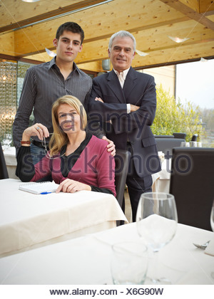 Mother Father and Son in a Restaurant. Handing down the business - Stock Photo