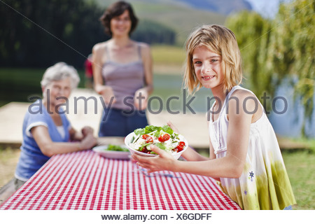 Girl holding salad at picnic table - Stock Photo