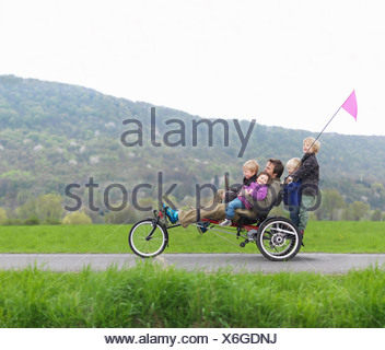 Family riding together on three wheeled bicycle - Stock Photo