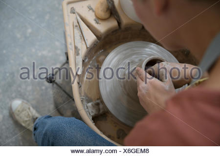Female potter using pottery wheel, shaping wet clay - Stock Photo