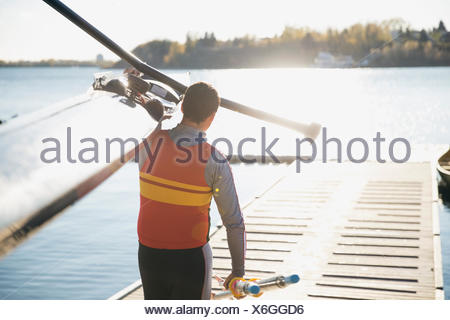 Rower carrying scull on dock at waterfront - Stock Photo