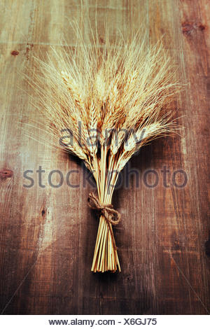 Wheat ears on wooden background - Stock Photo