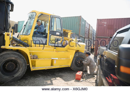 Mechanics fixing heavy machinery in sunny industrial container yard - Stock Photo