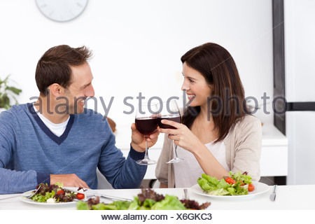 Lovely couple clinking glasses of red wine during lunch - Stock Photo