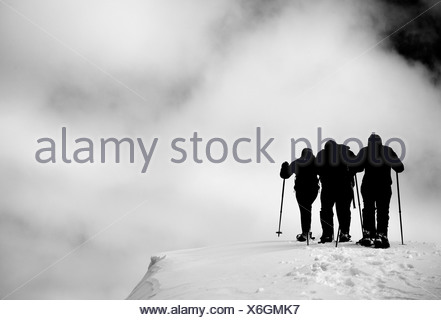 A group out snow shoeing on an overcast day. - Stock Photo