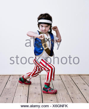 A boy in fancy dress costume, striped trousers and a belt, dressed as a pirate. - Stock Photo