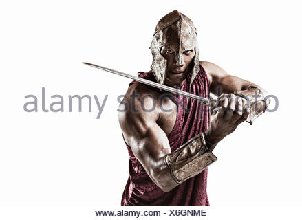 Studio portrait of muscular young man dressed as gladiator with helmet and sword - Stock Photo