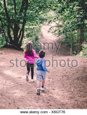 Rear view of two children running in woods - Stock Photo
