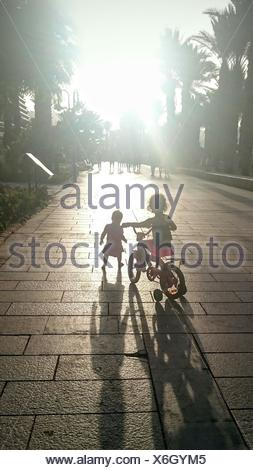 Rear View Of Two Children With Bicycle Outdoors - Stock Photo
