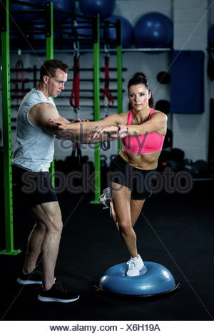 Trainer assisting a woman standing on a bosu ball - Stock Photo