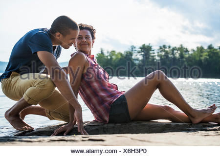 A couple close together by a lake in summer. - Stock Photo