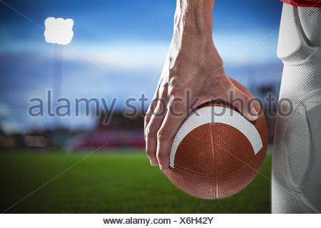 Composite image of sports player holding ball - Stock Photo