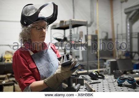 Senior female welder examining steel part in workshop - Stock Photo