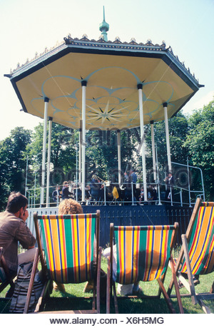 Bandstand, Kensington Gardens London England UK spectators brass band music musician musicians deckchair deckchairs English park - Stock Photo