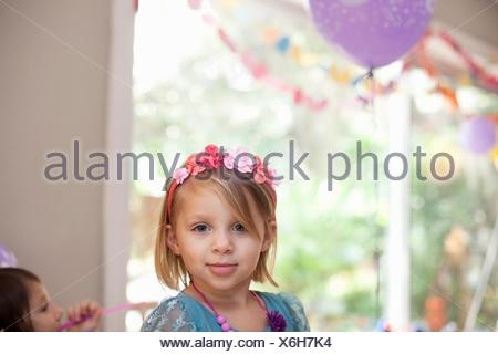 Portrait of blonde girl with flower headband smiling at camera - Stock Photo