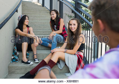Teenagers talking on stairs - Stock Photo
