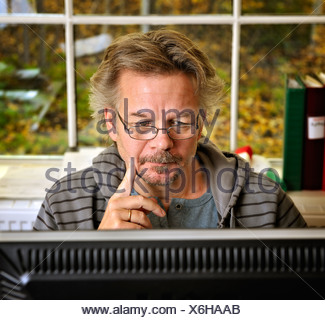 Middle-aged man in glasses using a computer - Stock Photo