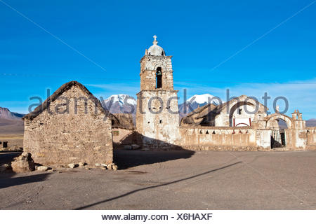 The church of Sajama and volcano Parinacota and Pomerape (Les Nevados de Payachatas). The Sajama Pueblo, in the Sajama National Parc, is the starting point of the climb of Nevado Sajama, the highest peak in Bolivia (6542m) - Bolivia, South America - Stock Photo
