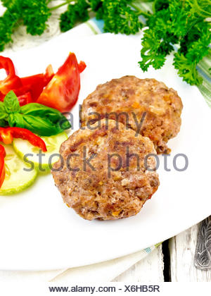 Cutlets stuffed with basil in white plate on board - Stock Photo