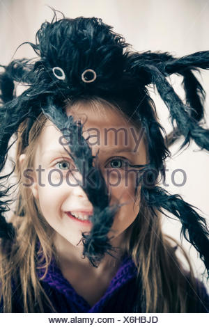 Smiling little girl with toy spider on her head - Stock Photo