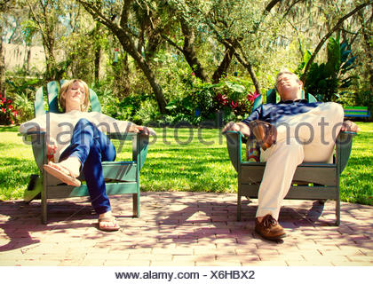 Mature couple sitting in garden chairs - Stock Photo