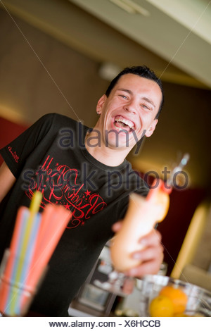 barkeeper serving a cocktail with a smile - Stock Photo