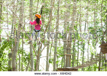 Little Chinese girl playing in tree top adventure park - Stock Photo
