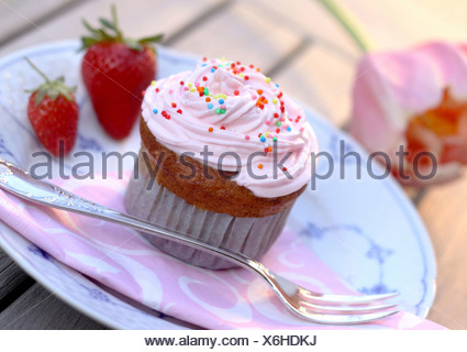 Cupcake muffin with cream, strawberries and pearl sugar on plate - Stock Photo
