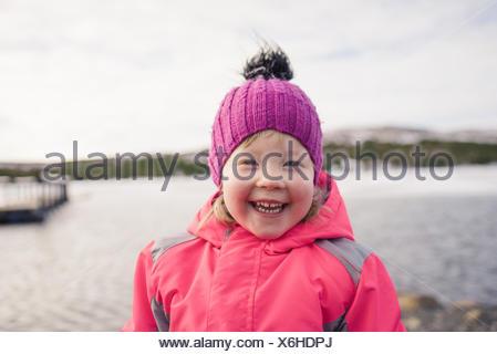 Portrait of girl wearing knit hat looking at camera smiling Reykjavik, Iceland - Stock Photo