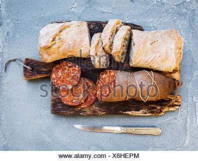 Wine snack set. Hungarian mangalica pork salami sausage and rustic bread on dark wooden board over a rough grey-blue concrete ba - Stock Photo
