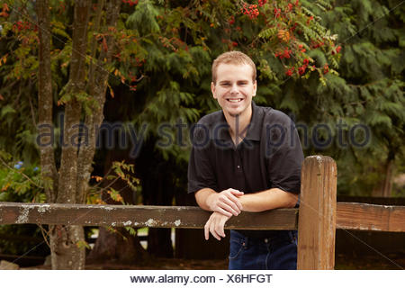 Young man leaning against wooden fence in forest - Stock Photo