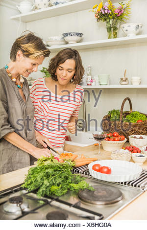 Senior woman and daughter preparing fresh vegetables in kitchen - Stock Photo