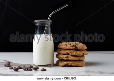 Stacked Chocolate chip cookies and milk in a vintage bottle with a straw - Stock Photo