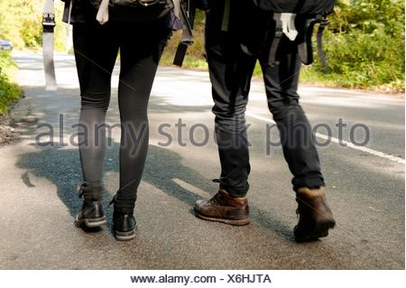 Waist down rear view of young hiking couple on rural road - Stock Photo